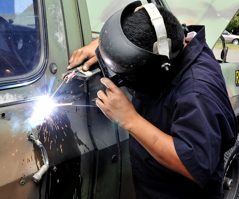 A Honduran Air Force metal worker fixes the holes needed to mount an antennae bracket on the tactical communication vehicle at Col. Hernán Acosta Mejia Air Base, Tegucigalpa, Honduras, Feb. 7.  Approximately 20 members of Air Mobility Command's 571st Mobility Support Advisory Squadron, 615th Contingency Response Wing, Travis AFB, Calif., are participating in a month-long Building Partner Capacity mission in Tegucigalpa, Honduras.  (U.S. Air Force photo by Tech. Sgt. Lesley Waters)