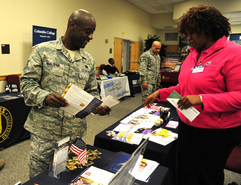 Tech. Sgt. Kevin McAlister picks up program information from one of the booths at the Education Fair held at Joint Base Charleston – Air Base Feb. 10.  The fair was open to all military, family members and retirees. Thirty four colleges and universities participated. McAlister is the 315th Airlift Wing Force Support Squadron support staff non-commissioned officer in charge.  (U.S. Air Force photo/ Staff Sgt. Nicole Mickle)