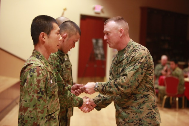Colonel Scott D. Campbell, commanding officer, 15th Marine Expeditionary Unit, presents his challenge coin to three soldiers from the Japanese Ground Self Defense Force for their hard work and dedication to Exercise Iron Fist 2012, during a social event, Feb. 14. The social event was held to celebrate the success of Exercise Iron Fist, a bilateral training event between the U.S. and Japanese Forces.