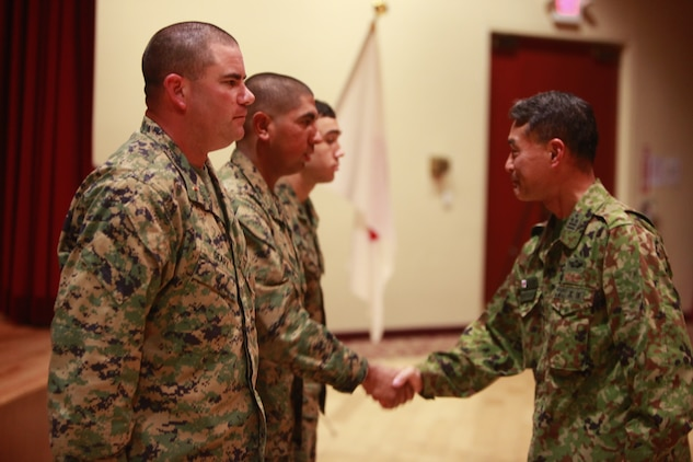 Japanese Army Col. Akira Kurosawa, commanding officer, Western Army Infantry Regiment, Japanese Ground Self Defense Force, presents his challenge coin to three Marines for their hard work and dedication to Exercise Iron Fist 2012, during a social event, Feb. 14. The social event was held to celebrate the success of Iron Fist, a bilateral training event between the U.S. and Japanese Forces.