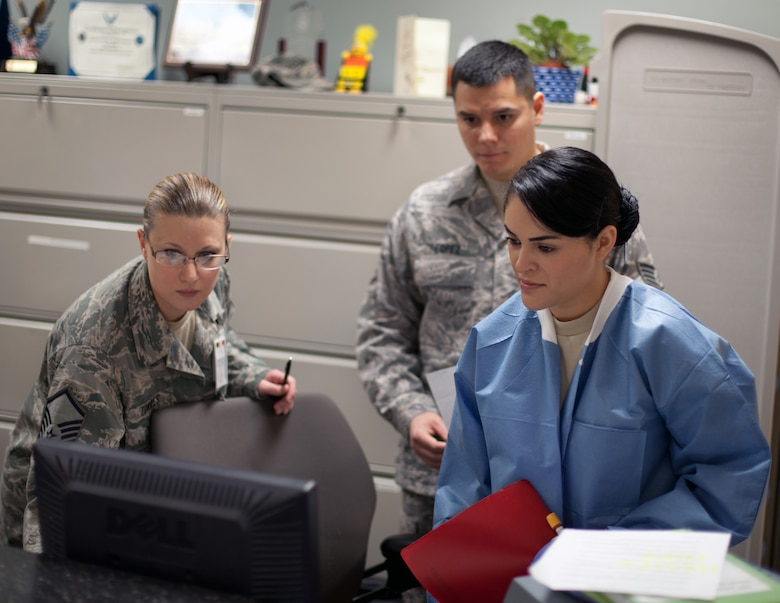 Master Sgt. Sarah Torres, noncommissioned officer in charge of the 349th Aeromedical Medicine Squadron's clinical laboratory, helps Staff Sgt. Daniel Lopez and Senior Airman Veronica Barros work through a computer procedure at the front window of the lab at David Grant USAF Medical Center. (U.S. Air Force photo / Lt. Col. Robert Couse-Baker)