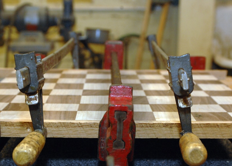 A two-tone chess board pressed between clamps dries at the Hobby Shop on Barksdale Air Force Base, La., Feb. 15. A variety of objects are made at the Hobby Shop by wood-working experts and Airmen qualified to use the Hobby Shop tools. (U.S. Air Force photo/Airman 1st Class Joseph A. Pag?n Jr.)(RELEASED)