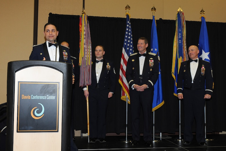 Lt. Col. Jay Sabia, 4th Fighter Squadron commander, acknowledges the 4 FS achievement upon receiving the 388th Fighter Wing Squadron of the Year honors. Master Sgt. Kristopher Kiger holds the guidon for the 4 FS after the honorary stream was added to it. USA photo by Alex Lloyd.