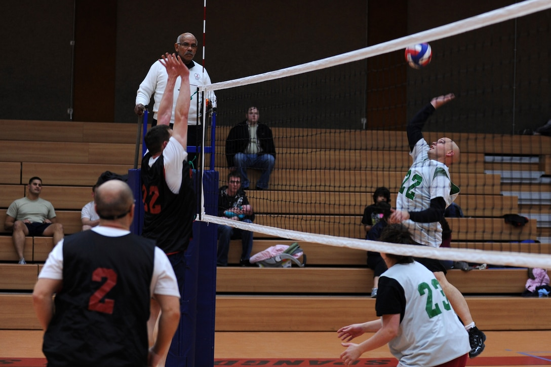 SPANGDAHLEM AIR BASE, Germany – Troy Soeder, 606th Air Control Squadron, number 22, jumps to hit the volleyball over 52nd Force Support squadron defenders during an intramural volleyball game at the Skelton Memorial Fitness Center here Feb. 15. FSS defeated ACS in two sets, 25-16 and 26-24.  This match kicked off the intramural volleyball season, and games will be played Monday – Thursday beginning at 6:30 p.m. at the fitness center. (U.S. Air Force photo by Airman 1st Class Matthew B. Fredericks/Released)