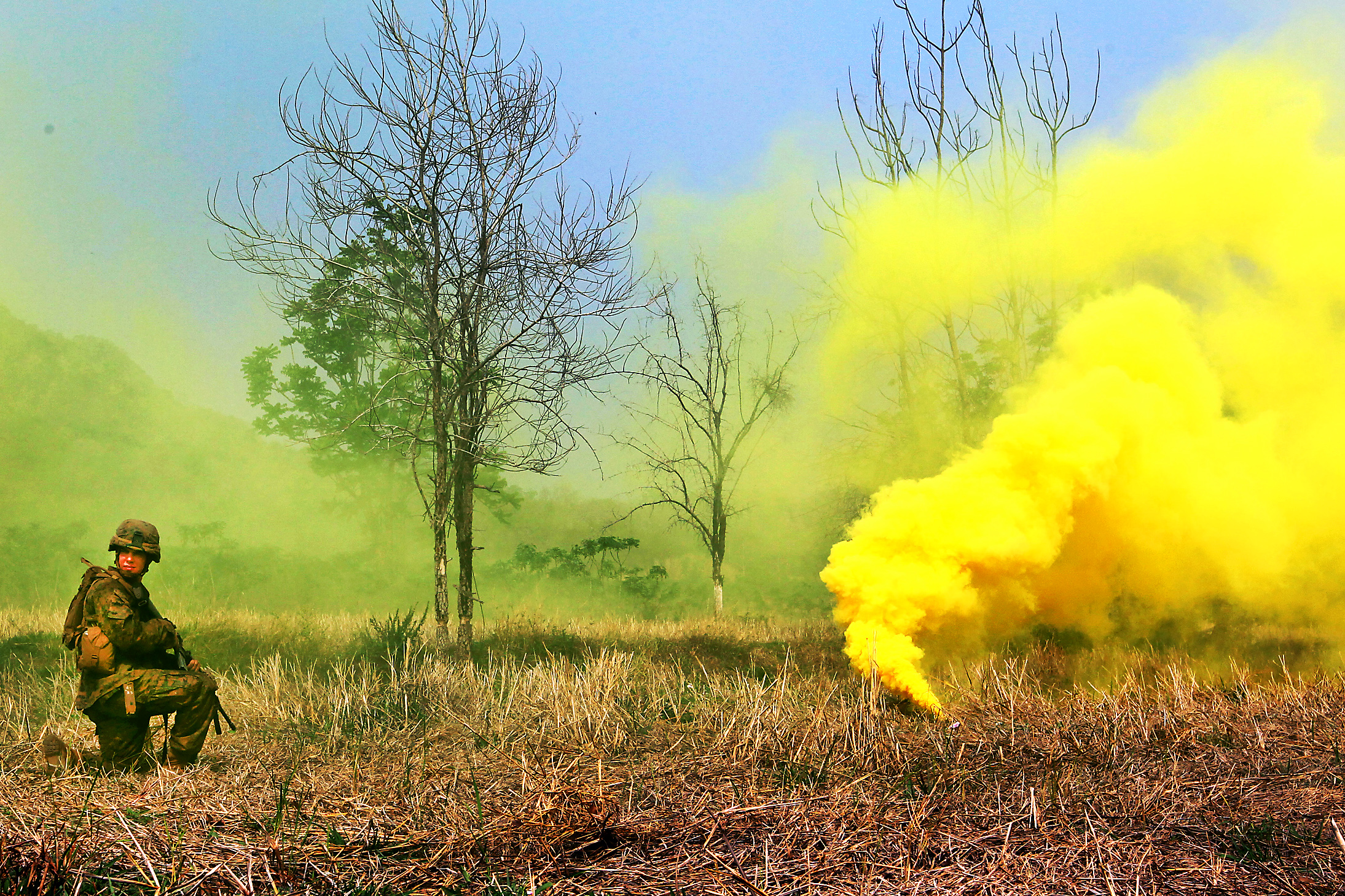 A U S  Marine provides security as yellow smoke signals supporting