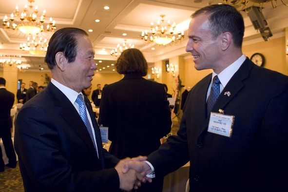 Moon Dong-Shin, mayor of Gunsan, Republic of Korea, and Col. Scott Pleus, 8th Fighter Wing commander, greet each other during the Korean and American Friendship Council Annual Friendship Night, Feb. 14, 2012. The banquet took place at the Rits-Plaza Hotel in Gunsan City, where 60 top Korean government officials from Gunsan City and local civic leaders showed their support and appreciation to the men and women stationed at Kunsan Air Base, ROK. (Courtesy photo/Gunsan City Hall)