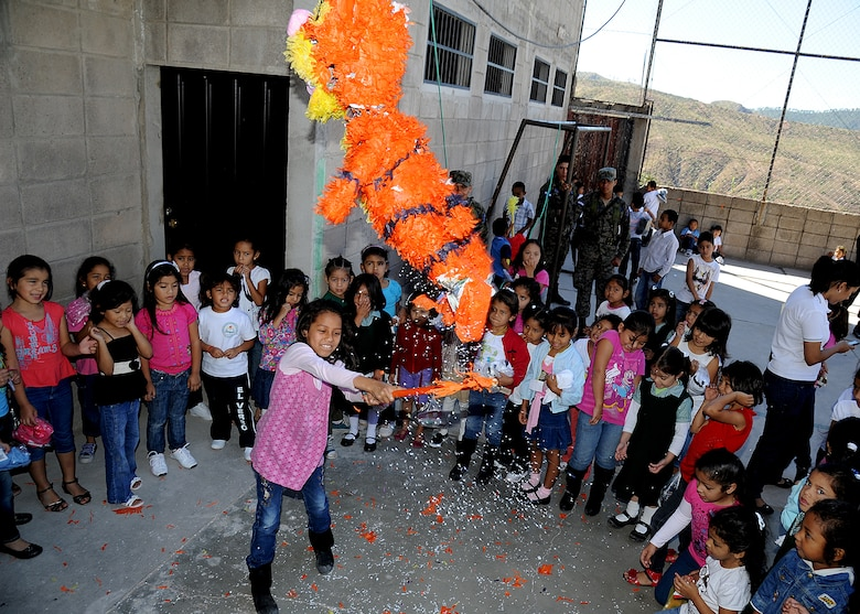 A student at the Instituto Evangélico El Verbo, located in Colonial Nueva Suyapa, takes a swing at a piñata during the Honduran Air Force and 571st Mobility Support Advisory Squadron visit to the school, Feb. 17.  More than 20 air advisors from the Air Mobility Command's 571st Mobility Support Advisory Squadron and Airmen from the Honduran Air Force extended their building partner capacity mission to the community by visiting two Honduran schools Feb. 14 and 17.  (U.S. Air Force photo by Tech. Sgt. Lesley Waters)