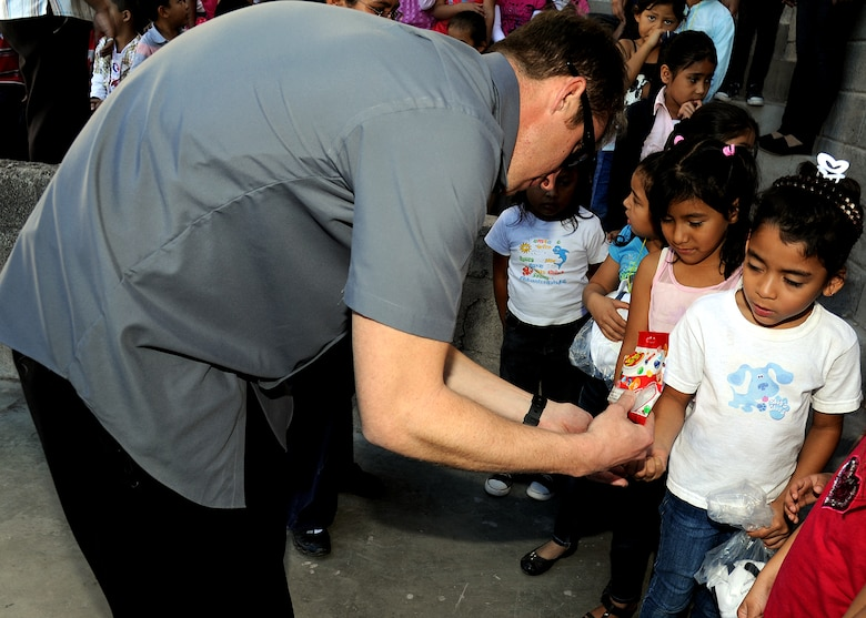 Tech. Sgt. Jeffrey Wright, 763rd Aircraft Maintenance Squadron rotor wing air advisor, Nellis AFB, Nevada, gives students at the Instituto Evangélico El Verbo some jelly beans which were given to the Honduran Air Force as a donation to the school Feb. 17.  Instituto Evangélico El Verbo is sponsored by Stewardship of Christian Ministries, which is a non-governmental Christian organization that promotes the development for some of the less fortunate families in Nueva Suyapa community.  (U.S. Air Force photo by Tech. Sgt. Lesley Waters)
