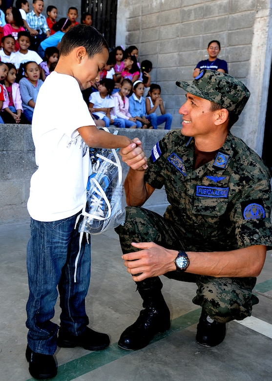 A student at the Instituto Evangélico El Verbo thanks a Honduran Air Force Airmen for the new shoes during the Honduran Air Force and 571st Mobility Support Advisory Squadron visit to the school Feb. 17.  The Honduran and U.S. Airmen enhanced that partnership by distributing donated children's clothes, shoes, soccer balls, and jelly beans to more than 90 children at Instituto El Cordero, in Colonial Flor De Campo and Instituto Evangélico El Verbo, in Colonial Nueva Suyapa.  (U.S. Air Force photo by Tech. Sgt. Lesley Waters)