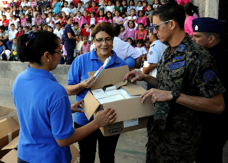 Maritsa Sauceda and Elia Ramona Cruz de Landa, Honduran Air Force officer spouses' society members, look through some of the donated items before distributing them to the students at the Instituto Evangélico El Verbo, in the Nueva Suyapa community of Tegucigalpa, Honduras, Feb. 17.  More than 20 air advisors from the Air Mobility Command's 571st Mobility Support Advisory Squadron and Airmen from the Honduran Air Force extended their building partner capacity mission to the community by visiting two Honduran schools Feb. 14 and 17.  (U.S. Air Force photo by Tech. Sgt. Lesley Waters)