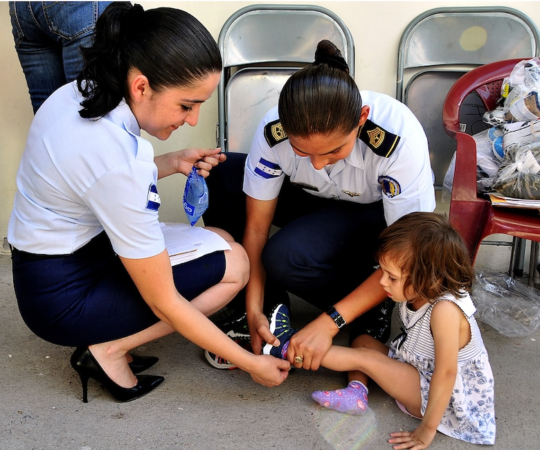 Two Honduran Air Forces Airmen work together and help a girl put her new shoes on which were donated to the Honduran Air Force to give to the Instituto El Cordero, in Tegucigalpa, Honduras, Feb. 14.  The Instituto El Cordero, sponsored by Association for World Services, is a school for children of single mothers.  (U.S. Air Force photo by Tech. Sgt. Lesley Waters)