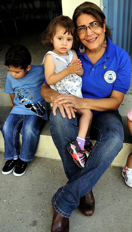 Elia Ramona Cruz de Landa, Honduran Air Force officer spouses' society president, holds a little girl during the visit of the U.S. and Honduran Air Force Airmen to the Instituto El Cordero, in Tegucigalpa, Honduras, Feb. 14.  (U.S. Air Force photo by Tech. Sgt. Lesley Waters)