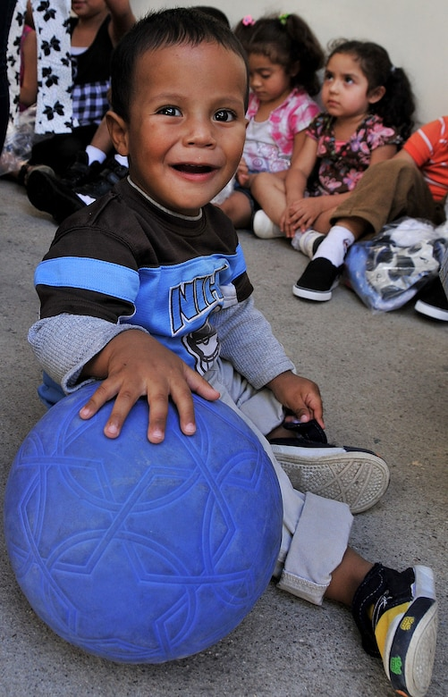 A toddler at the Instituto El Cordero maintains control of one of the soccer balls given to the school by the Honduran Air Force Feb. 14.  More than 20 air advisors from the Air Mobility Command's 571st Mobility Support Advisory Squadron and Airmen from the Honduran Air Force extended their building partner capacity mission to the community by visiting two Honduran schools Feb. 14 and 17.  (U.S. Air Force photo by Tech. Sgt. Lesley Waters)