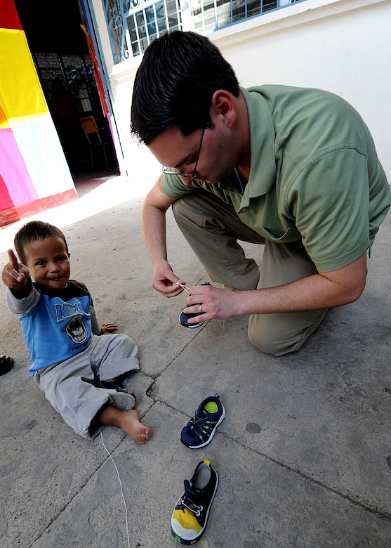 Tech. Sgt. Brian De Luca, 571st Mobility Support Advisory Squadron radio frequency transmission systems air advisor, puts shoes on a toddler at the Instituto El Cordero, in Tegucigalpa, Honduras, Feb. 14.  The Instituto El Cordero, sponsored by Association for World Services, is a school for children of single mothers.  (U.S. Air Force photo by Tech. Sgt. Lesley Waters)
