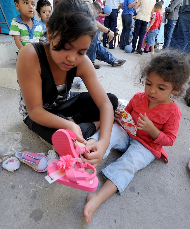 A teenager at the Instituto El Cordero helps another girl try on a new pair of sandals the Honduran Air Force delivered, with the help of the 571st Mobility Support Advisory Squadron, to the institute, in Tegucigalpa, Honduras, Feb. 14.  The Instituto El Cordero, sponsored by Association for World Services, is a school for children from single mothers.  (U.S. Air Force photo by Tech. Sgt. Lesley Waters)