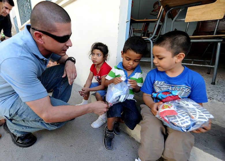 Staff Sgt. Jason Lares, 571st Mobility Support Advisory Squadron supply air advisor, works with the Honduran Air Force and hands out clothes to children at the Instituto El Cordero, in Tegucigalpa, Honduras, Feb. 14.  The Instituto El Cordero, sponsored by Association for World Services, is a school for children from single mothers.  (U.S. Air Force photo by Tech. Sgt. Lesley Waters)