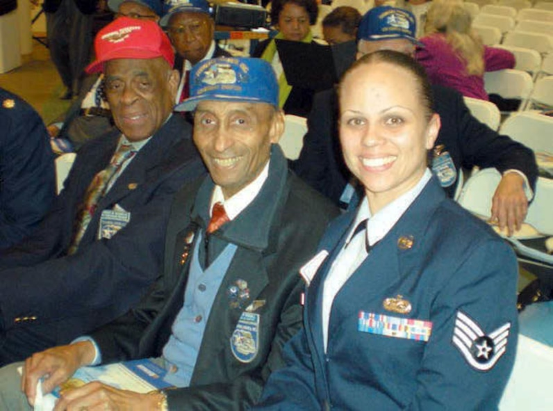 Staff Sgt. Aja Smith, 50th Aerial Port Squadron, March Air Reserve Base, Calif., sits beside Oliver Goodall (blue hat), Tuskegee Airmen, Los Angeles Chapter member and Edward W. Woodward, Tuskegee Airmen Western Region President at the Tuskegee Airmen International Convention. (U.S. Air Force photo/Staff Sgt. Aja Smith)
