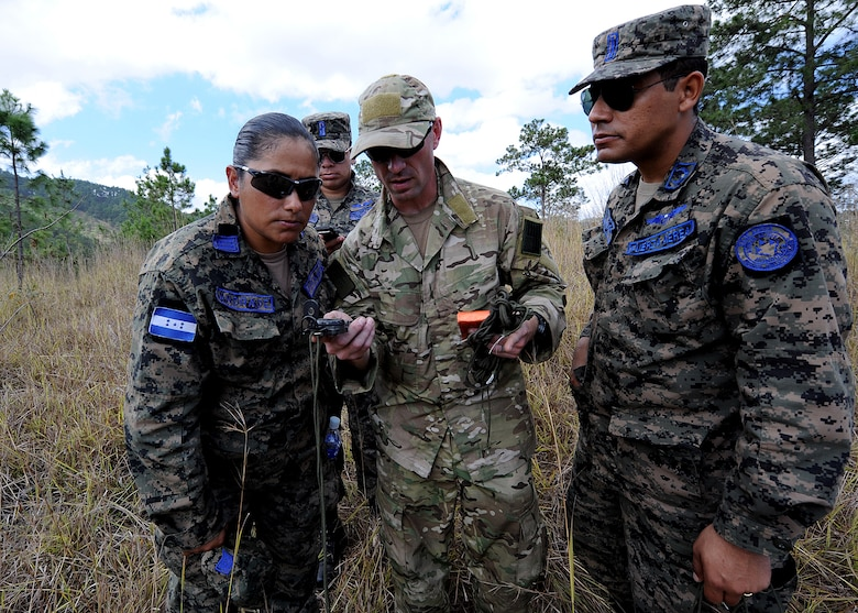 Staff Sgt. Daniel Foret, 571st Mobility Support Advisory Squadron Survival, Evasion, Resistance and Escape specialist air advisor, shows a Honduran Air Force pilots how to read a compass during the vectoring application of the aircrew survival seminar at Tamara, Honduras, Feb. 15.  (U.S. Air Force photo by Tech. Sgt. Lesley Waters)