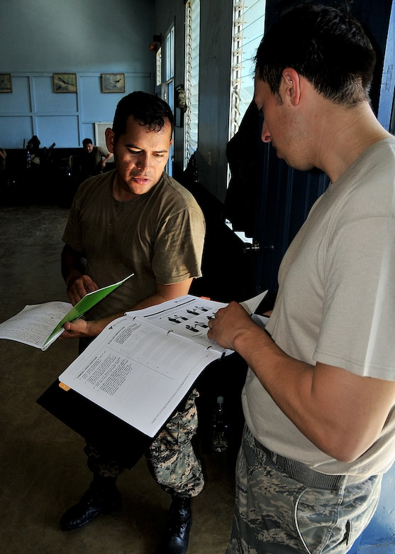 2nd Lt. Carlos Amador, Honduran Air Force installation security officer, compares his notes with Staff Sgt. Alejandro Gutierrez, 571st Mobility Support Advisory Squadron security forces air advisor, and the personal protection techniques manual as part of the self-protection portion of the air base defense seminar Feb. 14, during the Air Mobility Command Building Partner Capacity mission in Tegucigalpa, Honduras.  (U.S. Air Force photo by Tech. Sgt. Lesley Waters)