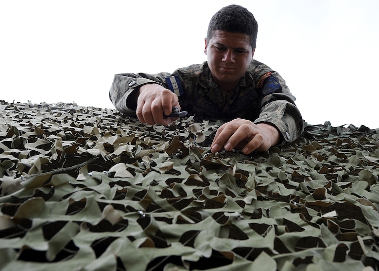 Staff Sgt. Miguel Fuentes, Honduran Air Force security forces member, secures two camouflage nets together as part of the tactical communication portion of the air base defense seminar Feb. 8, during the Air Mobility Command Building Partner Capacity mission in Tegucigalpa, Honduras.  (U.S. Air Force photo by Tech. Sgt. Lesley Waters)