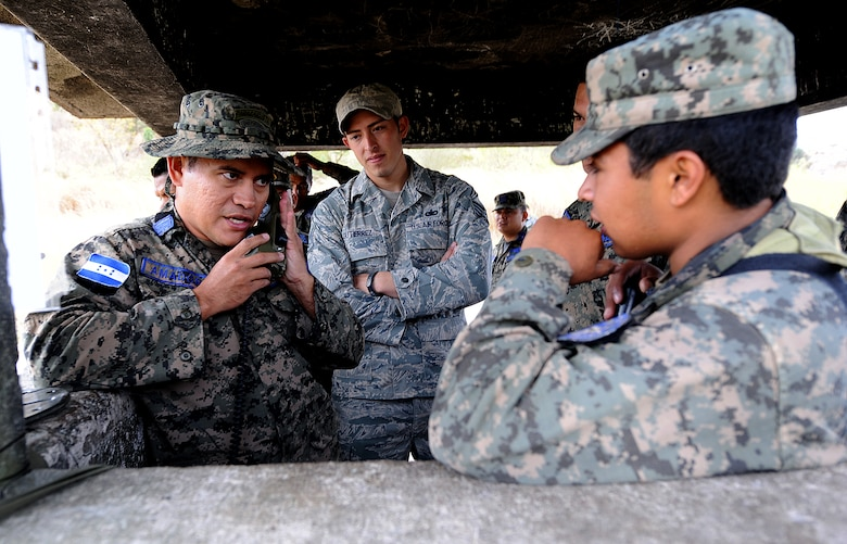 Staff Sgt. Alejandro Gutierrez, 571st Mobility Support Advisory Squadron security forces air advisor, looks on as 2nd Lt. Carlos Amador, Honduran Air Force installation security officer, shows a guard post sentry how to conduct a communications check as part of the tactical communication portion of the air base defense seminar Feb. 8, during the Air Mobility Command Building Partner Capacity mission in Tegucigalpa, Honduras.  (U.S. Air Force photo by Tech. Sgt. Lesley Waters)