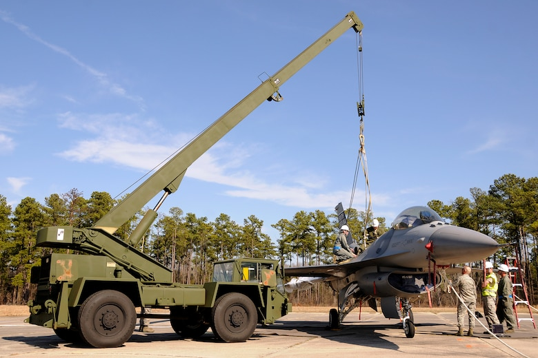 Crew Chiefs with the 169th Aircraft Maintenance Squadron at McEntire Joint National Guard Base, S.C., responds to a simulated aircraft mishap with a crashed F-16 fighter jet and UH-60 Black Hawk helicopter during a Crash, Damaged, Destroyed Aircraft Recovery (CDDAR) exercise on January 31, 2012.  The F-16 jet is connected to a crane to be transported from the accident sight. The training was important for all personnel involved due to the reality of the scenario, with the base sharing both air frames.(SCANG photo by TSgt. Caycee Cook)
