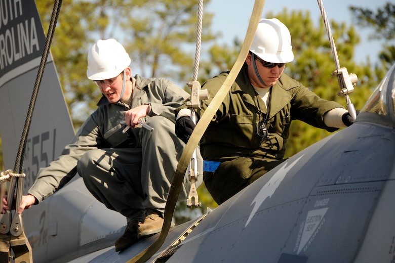 Airman 1st Class Casey Gray and Technical Sgt. Bronson Priebe, crew chiefs with the 169th Aircraft Maintenance Squadron at McEntire Joint National Guard Base, S.C., respond to a simulated aircraft mishap with a crashed F-16 fighter jet and UH-60 Black Hawk helicopter during a Crash, Damaged, Destroyed Aircraft Recovery (CDDAR) exercise on January 31, 2012.  A1C Gray and TSgt. Priebe connect straps to the F-16 jet so that it may be connected to a crane and transported from the accident sight. The training was important for all personnel involved due to the reality of the scenario, with the base sharing both air frames.(SCANG photo by TSgt. Caycee Cook)