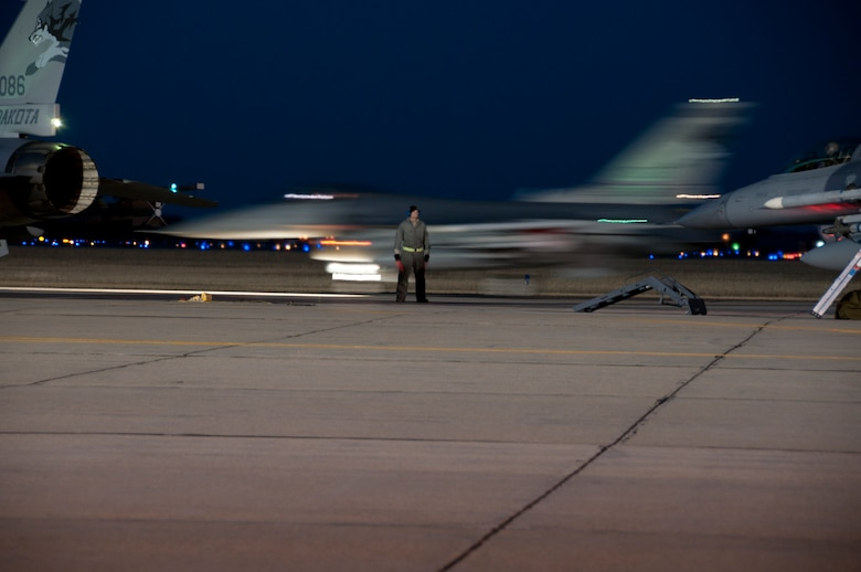 SIOUX FALLS, S.D. - As night falls on the ramp at Joe Foss Field, S.D., Technical Sgt. Ryan Bak, 114th Maintenance Group crew chief, prepares to assist with the taxi of an F-16 aircraft Feb. 16. The unit does night flying about once a month for a week in order to stay proficient with nighttime operations.(National Guard photo by Senior Master Sgt. Nancy Ausland)(Released)