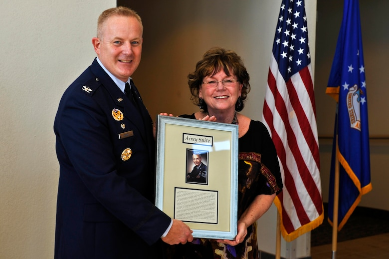 BUCKLEY AIR FORCE BASE, Colo.--  Colonel Daniel Dant, 460th Space Wing commander, presents a dedication plaque with Ellen Reid, daughter of the first Chief Master Sgt. of the Air Force, Paul W. Airey, Feb. 24, 2012. The dedication plaque will be displayed outside of the Airey Suite at the Rocky Mountain Lodge. (U.S. Air Force photo by Airman 1st Class Riley Johnson)