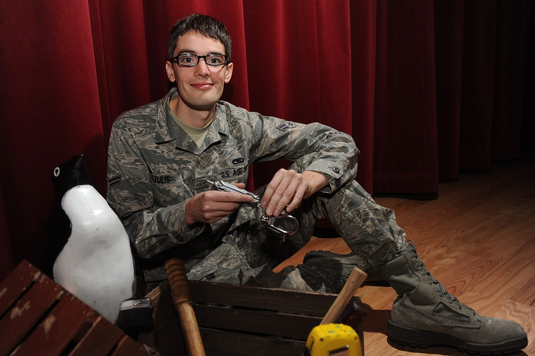 U.S. Air Force Airman 1st Class Nicholas Grazulis, 391st Aircraft Maintenance Unit weapons load crew member, poses for a picture while he sits amongst his hand-made theater props in the Gunfighter Service Center Feb. 24, 2012, at Mountain Home Air Force Base, Idaho. Grazulis was one of seven Airmen Air Force-wide selected to become a technician for Tops in Blue, an expeditionary entertainment unit that promotes community relations, recruiting and provides entertainment to Airmen and their families. (U.S. Air Force photo by Airman 1st Class Jonathan Glanville)
