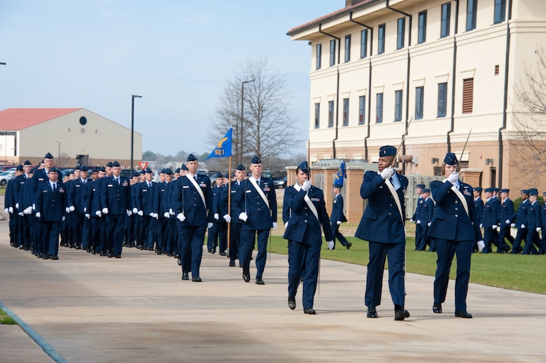 Basic Officer Training Course class 12-03 completes their graduation parade, with the two distinguished alumni reviewing the graduates Feb. 17. An A-10 flyover paid tribute to Johnson, a command A-10 pilot. (Air Force photo/Melanie Rodgers Cox)