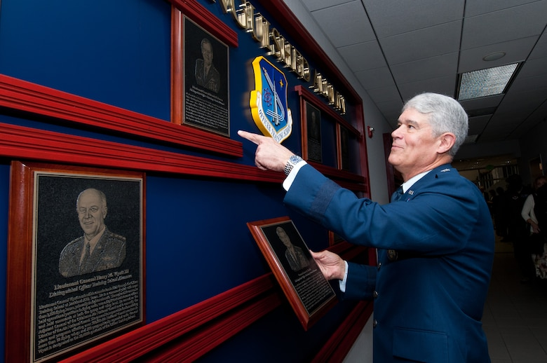 Retired Gen. Lance Smith looks at some of the plaques of Officer Training School distinguished alumni on display Feb. 17. He and Brig. Gen. Paul Johnson, currently deputy U.S. military representative to the NATO Military Committee at NATO Headquarters in Brussels, Belgium, were honored with an induction ceremony. (Air Force photo/Melanie Rodgers Cox)