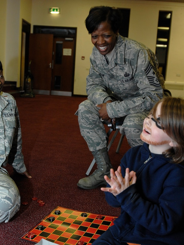 ROYAL AIR FORCE LAKENHEATH, England -- Chief Master Sgt. SaRita Lathan, 48th Fighter Wing command chief, chats with 6-year-old Gabriel Blankenship during the Deployed Spouses Dinner Feb. 15, 2012. The base hosts this special dinner quarterly for the spouses and children to show support and let the families know they're not forgotten while their loved ones are deployed.   (U.S. Air Force photo by Tech. Sgt. Lee A. Osberry Jr.)
