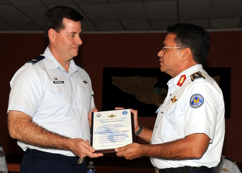 Brigadier Gen. Ruiz Pastor Landa Dubón, Honduran air force commanding general, presents Colonel Gary Gottschall, 615th Contingency Response Wing commander, a plaque and thanks him for the partnership between the two air forces during the closing ceremony in Tegucigalpa, Honduras, Feb. 23.  (U.S. Air Force photo by Tech. Sgt. Lesley Waters)