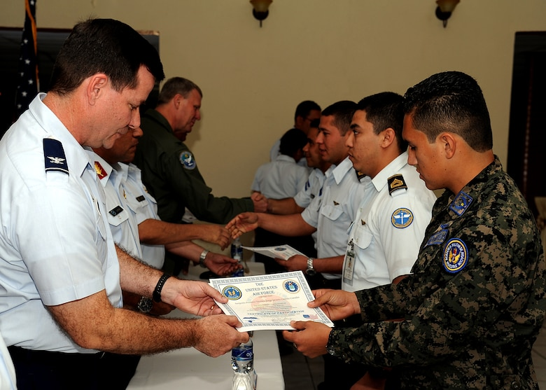 Colonel Gary Gottschall, 615th Contingency Response Wing commander, presents Sergeant First Class Jorge Jacinto Castillo Canales, Honduran air force member, with his certificate of participation during the closing ceremony, Tegucigalpa, Honduras, Feb. 23.  The building partner capacity mission, carried out by Air Mobility Command's two MSASs, was designed to promote regional stability by fostering key relationships and enhancing partner nation capabilities.  (U.S. Air Force photo by Tech. Sgt. Lesley Waters)