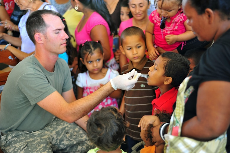 BELLA VISTA, Belize – U.S. Army CW2 Michael Spencer, 1st Battalion, 228th Aviation Regiment pilot, administers medication to a child during the first day of a joint medical readiness training exercise here with members from the Belize Ministry of Health, the Belizean military and Joint Task Force-Bravo, Soto Cano Air Base, Honduras Feb. 28. (U.S. Air Force photo/Staff Sgt. Bryan Franks)