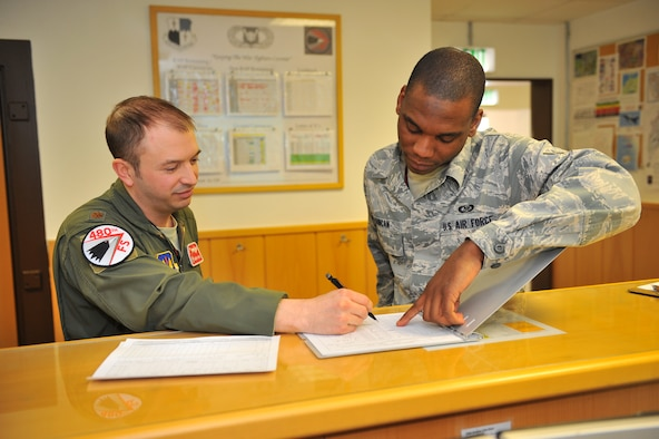 SPANGDAHLEM AIR BASE, Germany – Maj. Jason Hrynyk, left, 480th Fighter Squadron operations desk supervisor, and Airman 1st Class Keith Duncan, 480th FS aviation resource management apprentice, fill out a flight authorization form inside Bldg. 108 here Feb. 21 before adding the pilots' training hours to their records. Twelve Airmen work at the squadron's operations desk and are responsible for coordinating with base operations, weather operations and aircraft maintenance to ensure flight operations run smoothly. The operations desk is also responsible for gathering and organizing flight information to help log flight hours and brief pilots before, during and after flights. (U.S. Air Force photo by Airman 1st Class Dillon Davis/Released)