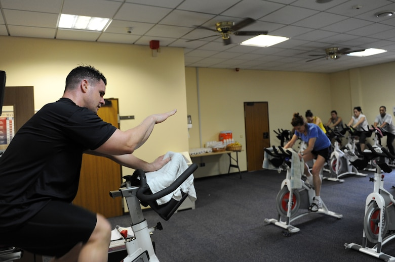 SPANGDAHLEM AIR BASE, Germany – Master Sgt. Mauli Martine, 52nd Logistics Readiness Squadron and spin instructor, leads the first hour of a spin-a-thon at the Skelton Memorial Fitness Center here Feb. 25. The spin-a-thon was a period of high-intensity indoor cycling that allowed members to challenge their cardio fitness with an option of signing up for one to three hours of spinning. Participants were guided by instructors through different workout phases with a variety of up-beat music. Spin class is one way to get a workout that burns calories and keeps bodies in shape offered at the fitness center. (U.S. Air Force photo by Senior Airman Christopher Toon/Released)