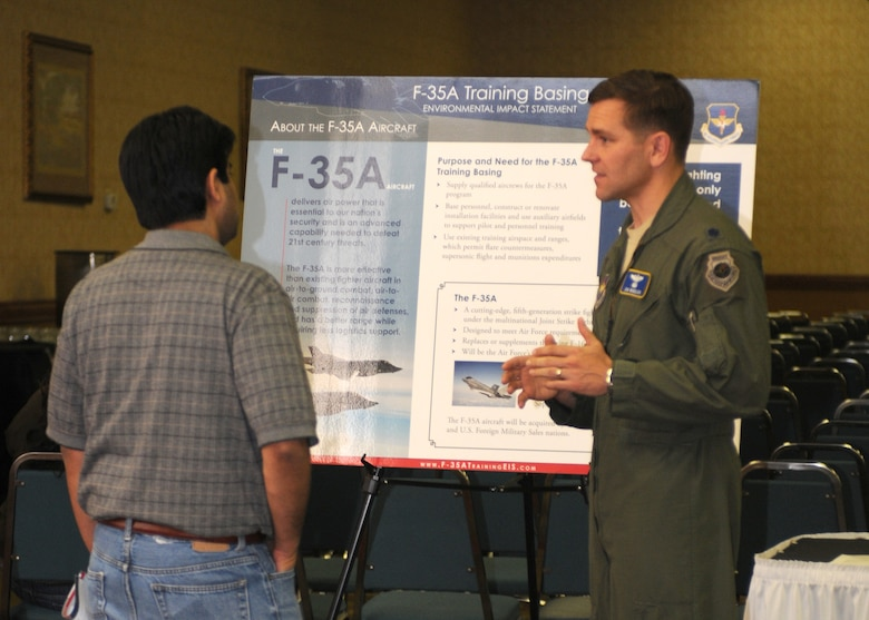 Lt. Col. Jon Wheeler, an F-35 instructor pilot assigned to Eglin Air Force Base, Fla., discusses the aircraft's capabilities with an interested member of the Tucson community Feb. 22 at a public hearing at the Holiday Inn near Tucson International Airport. Officials from the U.S. Air Force, Air Education and Training Command, and the 162nd Fighter Wing were available to answer questions and encourage public comment on the proposed basing of an F-35A Pilot Training Center at the Airport.  (U.S. Air Force photo/1st Lt. Angela Walz)