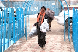 KABUL, Afghanistan — Orphans help carry loads of donated winter clothes into the facility from which eight U.S. Army Corps of Engineers employees from the Afghanistan Engineer District North distributed two dozen boxes of donated jackets, hats, gloves and other winter clothes to a large orphanage on Jan. 14, a day when heavy snow fell and the temperature reached 32 degrees in the Afghan capital.