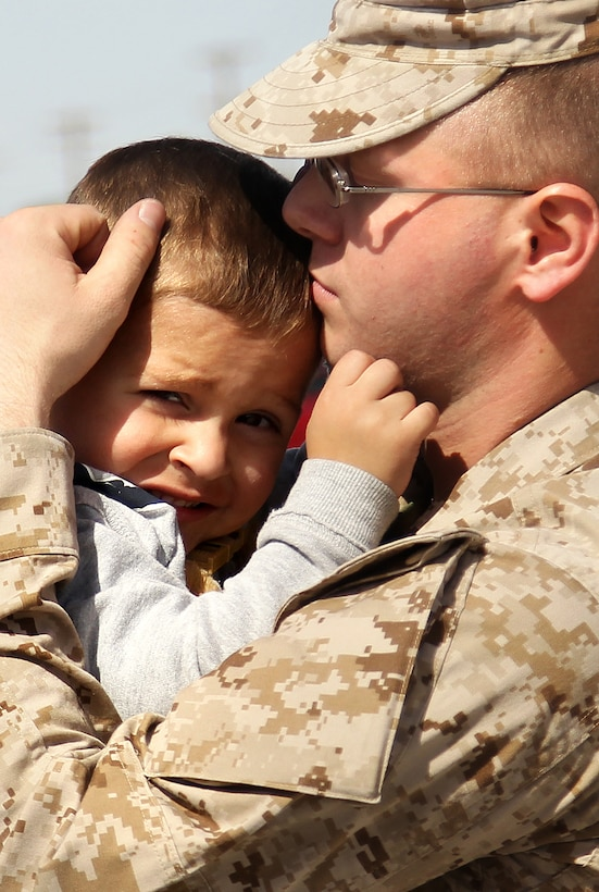 Lance Cpl. Joshua Slone, training noncommisioned officer, Headquarters and Service Co., 1st Battalion, 7th Marine Regiment, holds his son, Joseph, 3, one last time before departind with 1/7's advance party to Afghanistan Feb. 29, 2012.