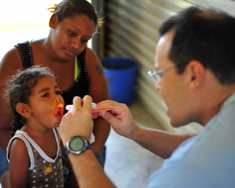 INDEPENDENCE, Belize - Dr. Ricardo Aviles, Medical Element doctor, examines a Belizean child on the final day of the two-day joint medical readiness training exercise here Feb. 29. (U.S. Air Force photo/Staff Sgt. Bryan Franks)