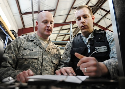 Tech. Sgt. Anthony Waldon assists Airman 1st Class Matthew Douglas with his paperwork during an inventory at the 628th Security Forces Squadron warehouse at Joint Base Charleston - Air Base Feb. 27. The warehouse coordinates daily, weekly and yearly accountability supply reports ensuring error free transaction processing for inventory totaling more than $3.2 million. Waldon is a 628th SFS supply non-commissioned officer in charge and Douglas is a 628th SFS journeyman. (U.S. Air Force photo/Staff Sgt. Katie Gieratz)