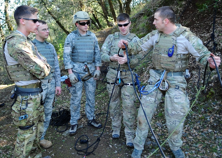 (Right) Staff Sgt. Scott Love, 9th Civil Engineer Squadron explosive ordnance disposal technician, explains the gear used to repel to fellow EOD Airmen during training in Auburn, Calif., Feb. 17, 2012. Love was preparing to repel down a more than 200 foot cliff with a simulated casualty. (U.S. Air Force photo by Senior Airman Shawn Nickel/Released)