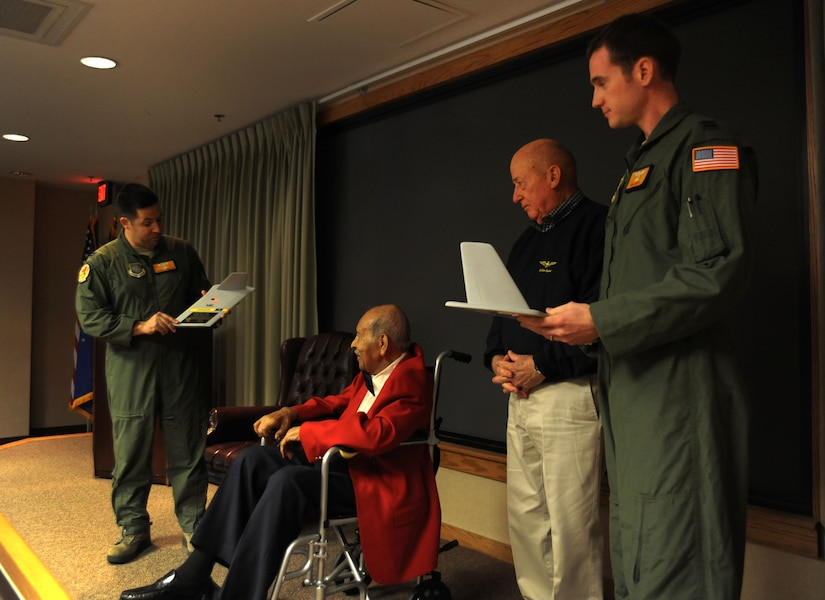 """Captains Joshua Pugliese and Benjamin Smith present Tuskegee Airman Eddie Gibson and Retired Rear Adm. James Flatley with a """"T Tail"""" memento at the 16th Airlift Squadron, 437th Airlift Wing deployment dinner at Joint Base Charleston - Air Base Feb. 16. More than 130 Airmen from the 16th AS deployed Feb. 24 to operate as part of the 816th Expeditionary Airlift Squadron. The 816th EAS supports intra-theater airlift, airdrop and aero-medical evacuation missions. Pugliese and Smith are from the 16th AS. Gibson served in the Army Air Corps as a bombardier-navigator, logged 2,300 flight hours and was awarded the Congressional Gold Medal for heroism. Flatley is the South Carolina Patriots Point Naval and Maritime Museum chief executive officer. During his career as a naval aviator he earned the Air Medal and Distinguished Flying Cross. (U.S. Air Force photo/Airman 1st Class Ashlee Galloway)"""