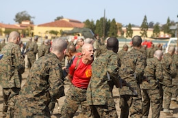 Sgt. William A. Getts, chief drill instructor, Company B, 1st Recruit Training Battalion, assists recruits by correcting them while they execute bayonet assault techniques as part of the Marine Corps Martial Arts Program training Feb. 29 aboard Marine Corp