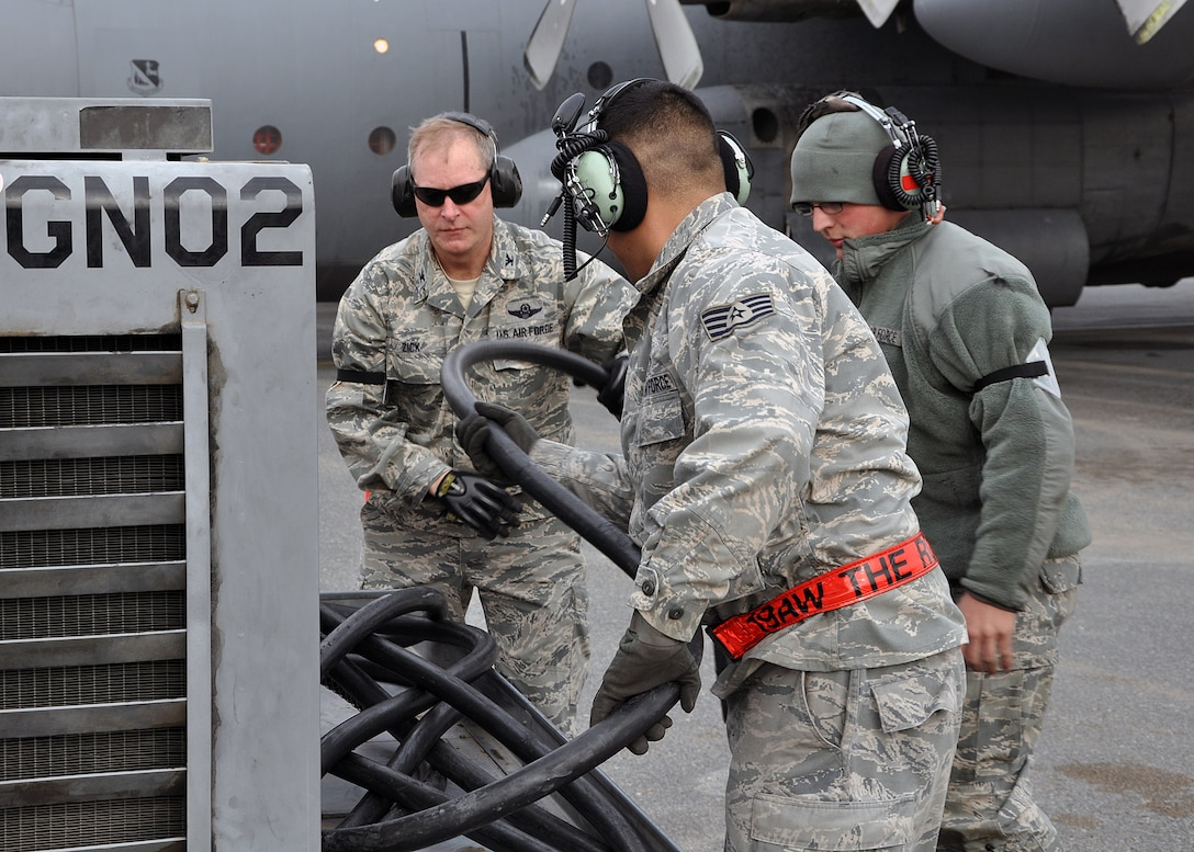 SOUTHWEST ASIA -- Col. Michael Zick, 386th Air Expeditionary Wing commander, assists Senior Airman Mathew Schmidt (right) and Staff Sgt. Julian Pacheco (center), 386th Expeditionary Aircraft Maintenance Squadron crew chiefs, disconnect a generator from a C-130 Hercules before its first flight of the new year, Jan. 1, 2012.  Zick volunteered to be an honorary crew chief for 2012's initial sortie, pulling parking chalks and marshalling the aircraft out of its parking spot and onto the flightline prior to takeoff. (U.S. Air Force photo/Tech. Sgt. Stacy Fowler)