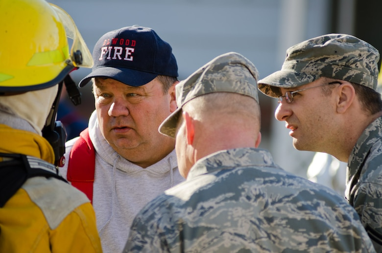 Alvin Wood, Elwood fire chief, talks with a local firefighter in Elwood, Kan., Jan. 5, 2012. Airmen from Rosecrans Air Guard Base, St. Joseph, Mo., assisted local fire departments with a residential fire. (Missouri Air National Guard photo by Staff Sgt. Michael Crane)