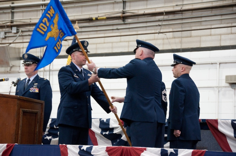 In a change of command ceremony on Otis Air National Guard Base, held on 7 January, 2012, Lt. Col David McNulty relinquishes command of the 102nd Intelligence Squadron by handing the squadron's guidon to 102nd Intelligence Group Commander Col. James Lefavor.