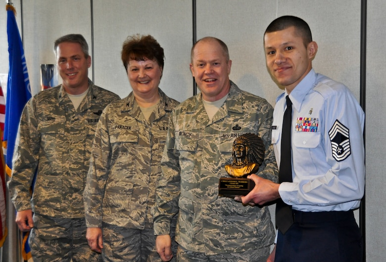 Command Chief Master Sgt. Christopher E. Muncy, command chief of the Air National Guard, presents recently promoted Chief Master Sergeant Antonio Marrero of the 128th Air Refueling Wing's medical group with a chief's bust in Milwaukee on January 08, 2012. 128 ARW Vice Commander Colonel Michael Mayo and Medical Group Commander Colonel Eileen Panacek provided a precursor history of the award and a list of accolades for CMSgt Marrero. Muncy was at the 128 ARW in part of tour of all the Air National Guard bases located in Wisconsin. USAF Photograph by Staff Sgt. Jeremy Wilson